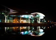 La costruzione moderna alla notte ha riflesso nel fiume immagine stock