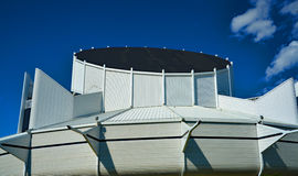 La costruzione moderna bianca con l'en indietro rotonda del cielo blu del tetto si appanna Fotografia Stock Libera da Diritti