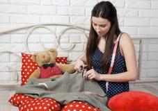 La costurera atractiva de la muchacha scissor la tela en cama Fotos de archivo libres de regalías