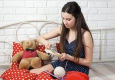 La costurera bonita de la muchacha enganchó a bordado en la cama Foto de archivo libre de regalías