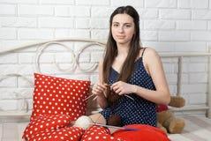 La costurera bonita de la mujer enganchó a hacer punto en una cama Foto de archivo libre de regalías
