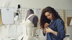 La costurera bonita joven está ocupada el ajustar de la ropa en la adaptación del maniquí con los pernos de costura Ropa del ` s  almacen de video