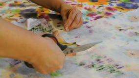 La costurera casera corta la tela con las tijeras Materia textil femenina del corte de la mano metrajes