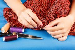 La costurera está cosiendo el paño por las manos Imagen de archivo