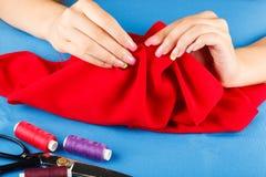 La costurera está cosiendo el paño por las manos Fotos de archivo