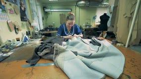 La costurera está cosiendo los abrigos de pieles en un taller metrajes