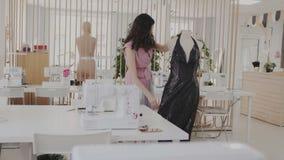 La costurera experta que comprueba y prueba un vestido de noche de moda en el vestido brillante oscuro del maniquí con una tela p almacen de metraje de vídeo