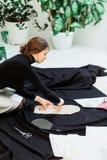 La costurera hermosa, cortó la tela negra en el piso del estudio fotos de archivo