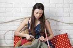 La costurera hermosa de la muchacha scissor la tela en cama Fotografía de archivo