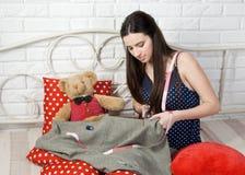 La costurera hermosa de la mujer joven scissor la tela en cama Fotografía de archivo