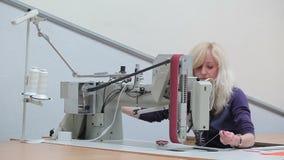 La costurera pone el paño en la máquina de coser almacen de video