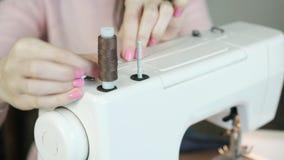 La costurera rebobina el hilo en la bobina en la máquina de coser metrajes