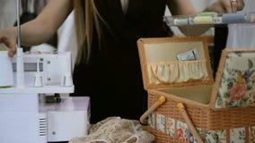 La costurera saca cuatro carretes blancos de hilo de la caja metrajes