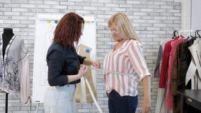 La costurera toma medidas con la cinta del cliente de la mujer en la adaptación del taller almacen de video