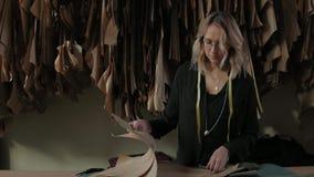 La costurera trabaja en un estudio de la textura, examina dibujos de la ropa almacen de video
