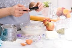 La cottura del blogger è cucinare alla cucina nel giorno soleggiato e sta facendo la foto allo smartphone del processo di cottura fotografia stock libera da diritti