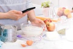 La cottura del blogger è cucinare alla cucina nel giorno soleggiato e sta facendo la foto allo smartphone del processo di cottura immagine stock libera da diritti