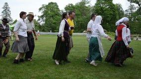 La cottura della fisarmonica del gioco del musicista dell'uomo e la gente ballano nelle paia video d archivio