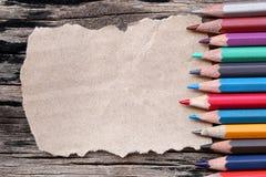 La couleur de plan rapproché crayonne la concaténation sur le papier brun et le vieux woode Images libres de droits
