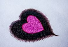 La couleur en bois tirée par la main crayonne, un coeur à un coeur sur le fond de livre blanc photographie stock
