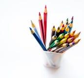 La couleur en gros plan crayonne dans un verre en plastique sur le fond Photographie stock libre de droits