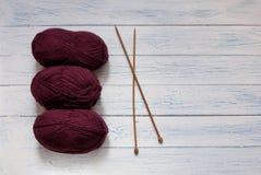 La couleur Maruni de fil et les aiguilles de tricotage sont dans le bureau blanc Images stock