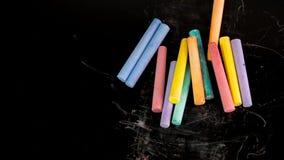 La couleur multi marque à la craie sur le fond noir pour l'espace de copie photographie stock libre de droits