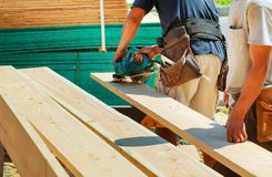 La coupe en bois avec la circulaire a vu le travailleur de sexe masculin ou l'homme pratique avec Image stock