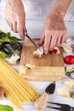 La coupe femelle de mains préparent des ingrédients pour des pâtes avec des champignons Images libres de droits
