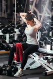 La coupure de la femme dans la séance d'entraînement pour attacher ses cheveux photos stock