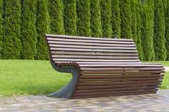 La courbe élégante a formé les meubles extérieurs bruns de banc en bois en parc comme fond d'image Photographie stock libre de droits