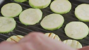 La courgette a découpé en tranches frit dans une casserole de gril banque de vidéos