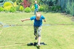 La course de deux frères autour sur la pelouse et le jeu avec de l'eau éclabousse Jour ensoleillé d'été images libres de droits