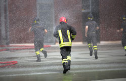 La course de sapeurs-pompiers sous éclabousse de l'eau pendant l'extingu du feu photo libre de droits