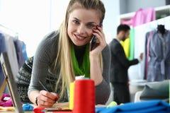 La coutume vêtx travailler le concepteur de service au téléphone images stock