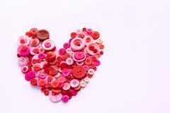 La couture rouge se boutonne dans la forme de coeur sur le fond blanc de modèle Image stock