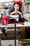 La couture vêtx de la belle jeune femme de brune d'atelier avec le ruban sur sa tête Images libres de droits