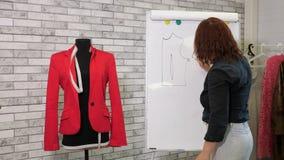 La couturière dessine un modèle de veste sur le conseil blanc dans l'atelier de couture banque de vidéos