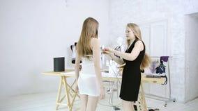 La couturière prend la femme de mesures pour les vêtements de couture dans le studio clips vidéos