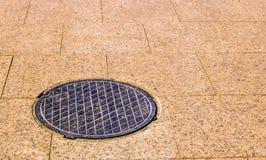 La covata del metallo in un pavimento dai blocchi di marmo Fotografie Stock Libere da Diritti