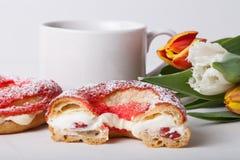La crème anglaise faite maison durcit avec de la crème et le groupe de tulipes de ressort dessus Image stock