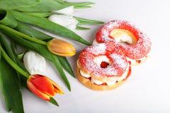 La crème anglaise faite maison durcit avec de la crème et le groupe de tulipes de ressort dessus Images libres de droits