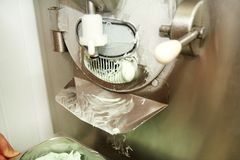 La crème glacée faisant la machine produit des saveurs en bon état de crème glacée et elle tombe dans le récipient en acier image libre de droits