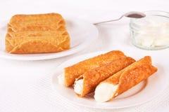 La crème a rempli ruptures d'eau-de-vie fine a servi d'un plat Ruptures non remplies et un pot avec de la crème à l'arrière-plan images stock