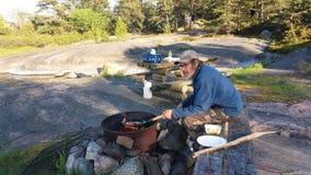 La crêpe de cuisson en feu est tout à fait commune dans l'été, dans de petites îles en Finlande Image libre de droits