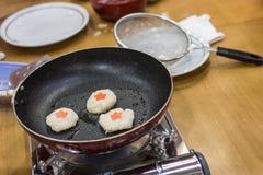 La crêpe de pomme de terre coréenne est faite frire utilisant une casserole noire image stock