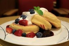 La crêpe pelucheuse Mouthwatering de soufflé avec les baies fouettées fraîches de crème et de mélange a servi du plat blanc photos libres de droits