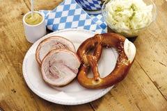 La cría del cerdo rueda, los pretzeles y ensalada de col en el tablero de madera Fotografía de archivo libre de regalías