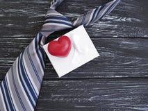 La cravate, coeur, symbole de fête de design de carte de boîte-cadeau romantique célèbrent le vieux fond en bois noir, jour heure Images stock