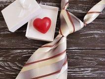 La cravatta, cuore, simbolo festivo del contenitore di regalo romantico celebra il vecchio fondo di legno nero, il giorno felice  Fotografia Stock